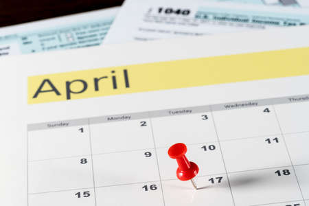 Calendar on top of form 1040 income tax form for 2017 showing tax day for filing is April 17 2018 Stock Photo