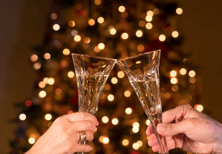 Caucasian senior married couple clink crystal champagne glasses against defocused xmas tree lights