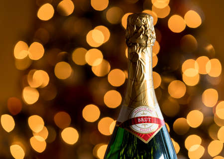 Bokeh lights from Christmas tree behind the gold foil covered neck of champagne bottle