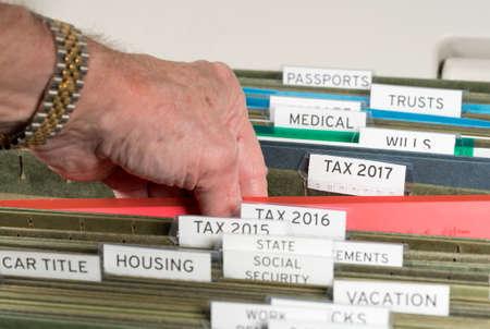 Close-up van een goed georganiseerd thuisarchiveringssysteem met tabbladen voor elk onderwerp en focus op belastingaangiftepapieren voor 2017