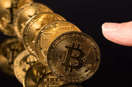 Bitcoin coins in a row on reflective surface with finger about to push them Zdjęcie Seryjne