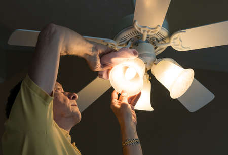 Senior adult male dusting the glass shade of a bulb in a ceiling fan and lighting fixture 写真素材
