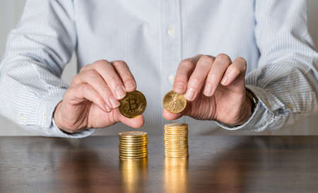 Senior man holding gold coins alongside stack of bitcoins to illustrate investment choice