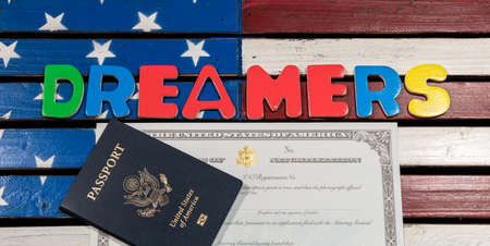 Dreamers concept on wooden USA flag with passport and naturalization certificate
