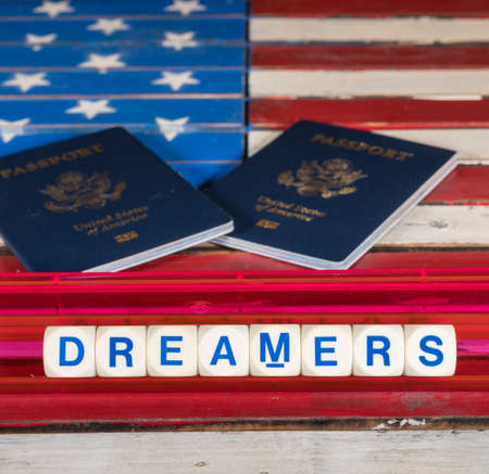Dreamers children spelling letters on wooden USA flag with passports for citizenship Stock fotó