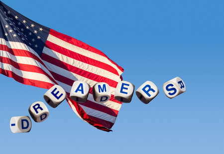 Dreamers children spelling letters on blue sky and USA flag to illustrate dreaming of the future