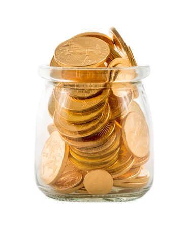 Pure gold US treasury coins inside a glass jar against a white background to represent investment or wealth Stock Photo