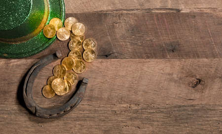 Treasure of pure gold coins from a green hat on rustic wooden table into horseshoe to celebrate luck on St Patricks Day Stock Photo