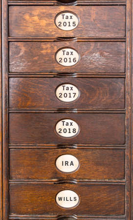 Wooden drawers of an ancient filing system with labels for income tax filing and pensions Imagens