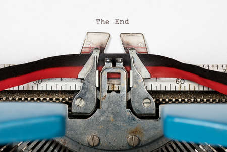 Macro detail of the ink ribbon and text of electric typewriter with words The End