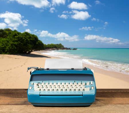 Modern electric typewriter on wooden desk with ocean beach background suggesting deserted island