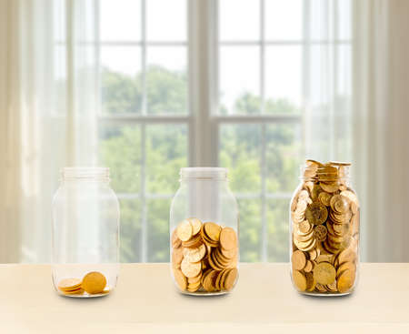 Concept of investment or savings for retirement with three glass jars filled with gold coins in front of bright window