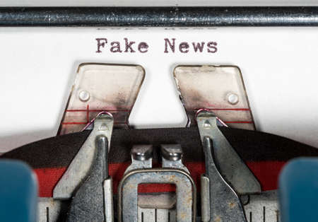 Macro detail of the ink ribbon and Fake News text of electric typewriter for newspaper media