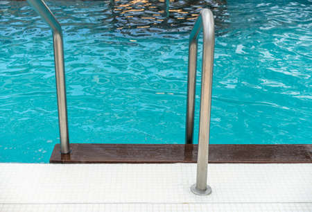 Stainless steel railings and teak steps into luxury swimming pool Stock Photo