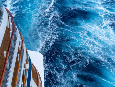 View down the floors of cruise ship at the powerful churning ocean behind the ship
