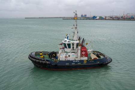 CADIZ, SPAIN - MARCH 14, 2018: Blue tug boat ready to tow cruise ship in harbour of Cadiz in Spain