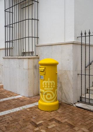 ARCOS DE LA FRONTERA, SPAIN - MARCH 14, 2018: Yellow traditional postbox in Arcos de la Frontera near Cadiz in Spain