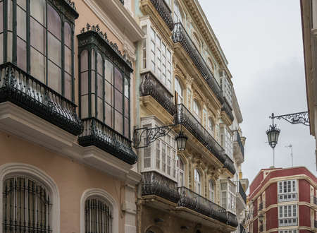 Cast iron balconies on Calla Ancha shopping street in city of Cadiz in Southern Spain Archivio Fotografico