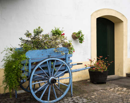 Blue wooden horse cart filled with flowers and plants by old white painted stone building with arches