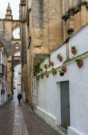Old man walks past Church of Santa Maria in Arcos de la Frontera near Cadiz in Spain Imagens