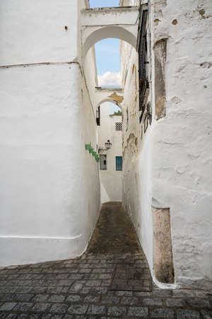 Narrow pathway with arch in Arcos de la Frontera near Cadiz in Spain