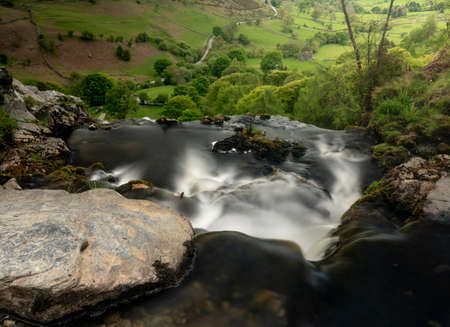 Smooth blurred motion stream falls into valley from the top of the Pistyll Rhaeadr waterfall in Wales