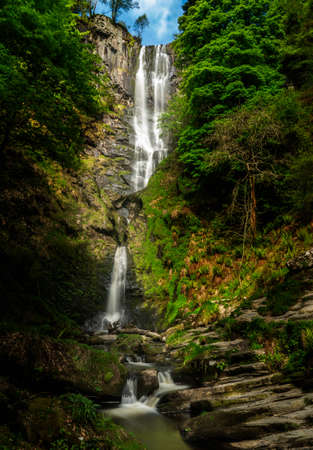 High falling water in waterfall and cascades at head of Pistyll Rhaeadr falls in Wales