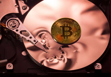 Bitcoin superimposed on the damaged discs of a hard drive storage to illustrate bitcoin market crash Stock Photo