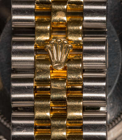 MORGANTOWN, WV - 24 JULY 2018: Mens Rolex gold watch band with focus on Crown icon
