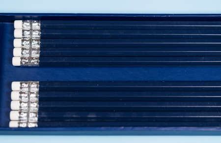 Row of new blue pencils lined up with erasers side by side. Copy space for message in gap