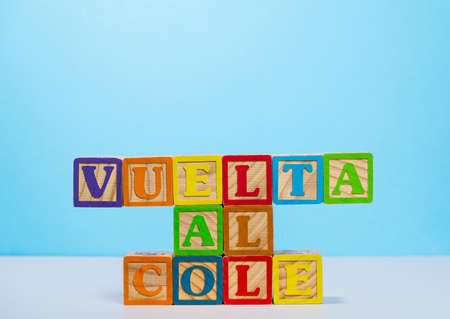 Vuelta al Cole translates to Back to School in spanish with wooden blocksagainst blue background with copy space
