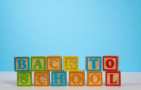 Stack of wooden blocks stacked to spell Back to School against blue background with copy space