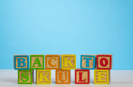 Stack of wooden blocks wrongly spelling Back to School as Skule against blue background with copy space