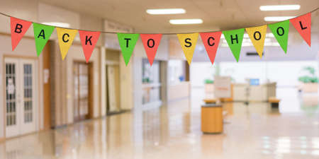 Colorful sack cloth pennants to create pennant flag message of Back to School above entrance of school corridor Stock Photo
