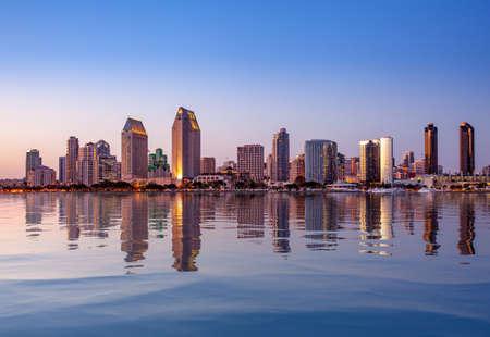 Sonnenuntergang, der die hohen Wolkenkratzer von San Diego in Kalifornien vom Centennial Park in Coronado mit künstlicher Wasserreflexion beleuchtet