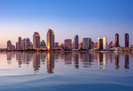 Sunset illuminating the tall skyscrapers of San Diego in California from Centennial Park in Coronado with artificial water reflection