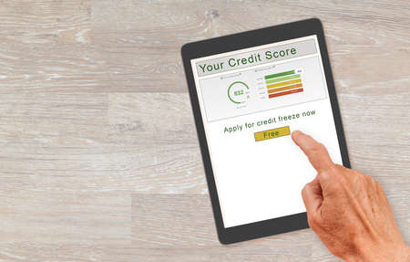 Computer tablet or smartphone with  credit score report and senior hand about to press button to freeze the record. New law allows free credit freezes with agencies