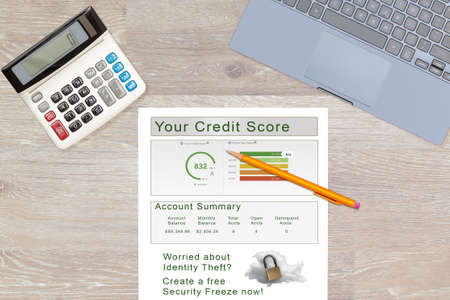 Laptop and calculator on desk with credit score report as concept for new law allowing free credit freezes with agencies