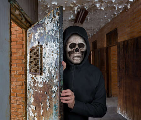 Halloween theme of man with skull welcoming visitors to haunted prison cell