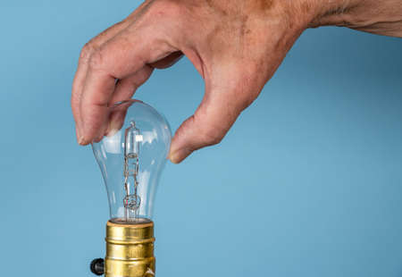 Senior caucasian man unscrewing a halogen lightbulb as concept for EU decision to ban the light bulbs Stock Photo
