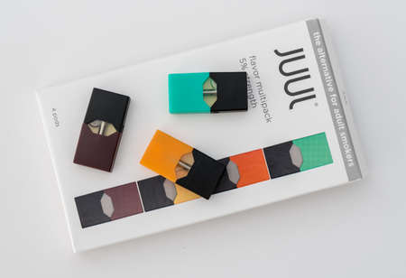 MORGANTOWN, WV - 25 AUGUST 2018: Juul e-cigarette or nicotine vapor dispenser box on and JUULpods on white background 写真素材 - 117822229