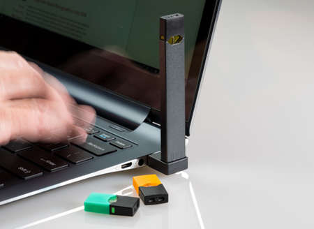 MORGANTOWN, WV - 27 AUGUST 2018: Juul e-cigarette or nicotine vapor dispenser being charged in modern laptop with JUULPods on white background