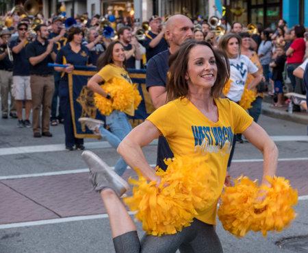 MORGANTOWN, WV - 5 OCTOBER 2018: Homecoming parade down Main Street of Morgantown with Alumni cheer leaders