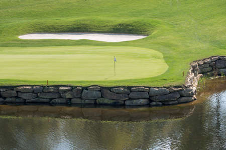 Flag and hole on a luxury golf course with water hazard and sand trap surrounding the green Imagens