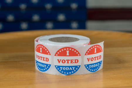 Large roll of I Voted Today stickers ready for voters in the US elections with flag in background