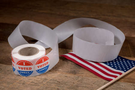 Large roll of I Voted Today stickers with many having been used for voters in the US elections with USA flag on table