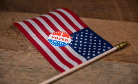 Narrow focus on I Voted Today sticker  for voters in the US elections with USA flag on rustic wooden table Banque d'images