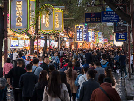 XIAN, CHINA - 17 OCTOBER 2018: Crowds of tourists by street food vendors in the Muslim quarter of Xian