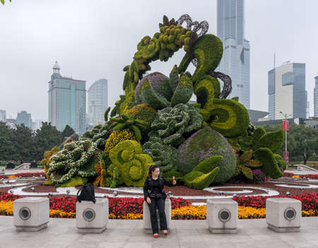 SHANGHAI, CHINA - 25 OCTOBER 2018: Tourist taking selfie by floral display by Shanghai Museum of Chinese Art Editorial