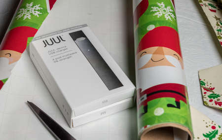 MORGANTOWN, WV - 22 DECEMBER 2018: Juul e-cigarette or nicotine vapor dispenser box being wrapped as xmas gift